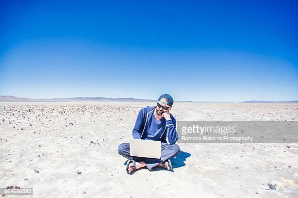 Man sitting cross legged in desert searching on laptop, Nevada, USA
