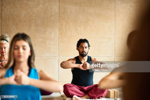 man sitting cross-legged in yoga studio - individuality stock pictures, royalty-free photos & images