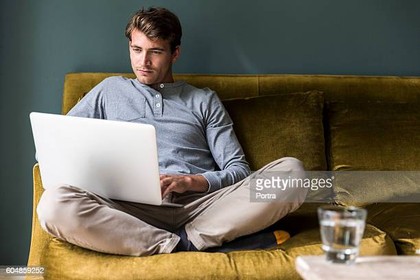 man sitting cross-legged while using laptop - using laptop stock pictures, royalty-free photos & images