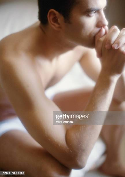 Man sitting holding hands to mouth, blurred.