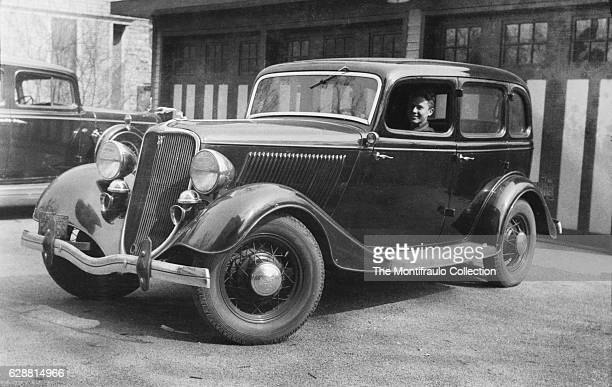 A man sitting in a 1934 Ford DeLuxe Fordor parked in front of garage doors The 34 Ford is infamous as the car that outlaws Bonnie and Clyde were...