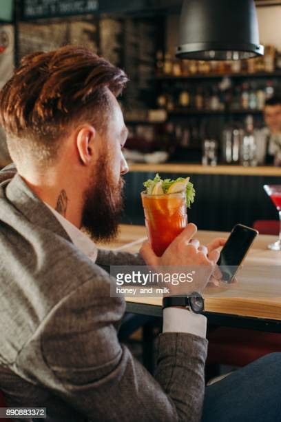 Man sitting in a bar looking at his mobile phone