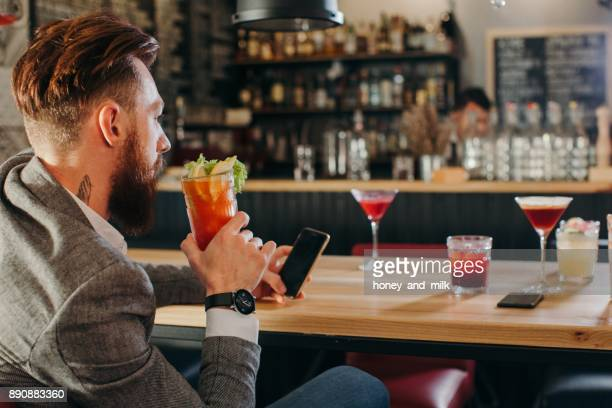 Man sitting in a bar looking at his phone