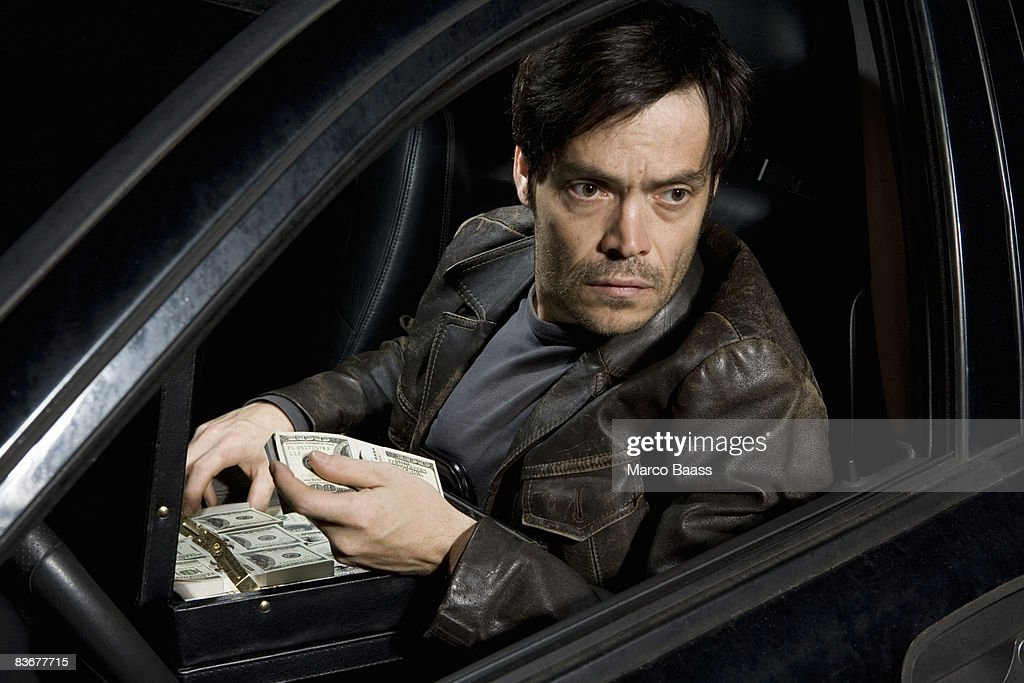 A man sitting in a car with an open briefcase full of money : Stock Photo