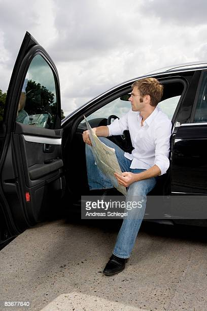 A man sitting in a car with the door open and reading a map