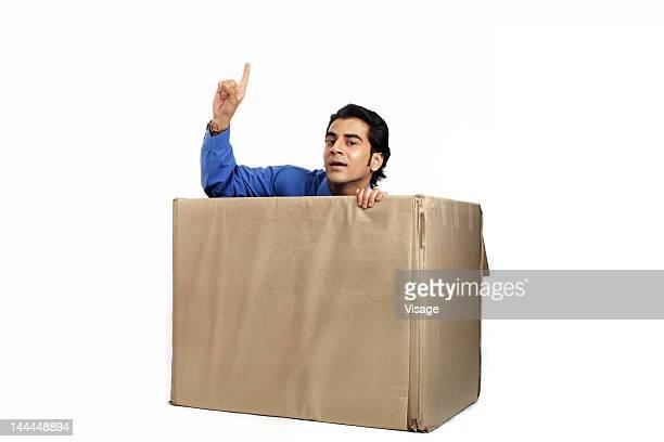 A man sitting in a cardboard box
