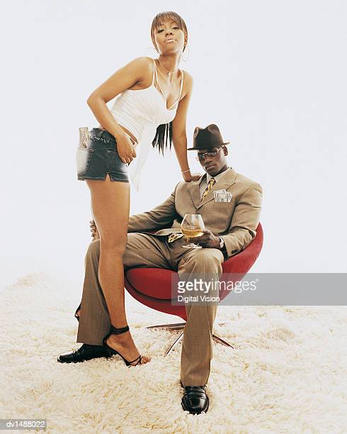 Man Sitting in a Chair With a Glass of Brandy Holding the Leg of a Woman With US Banknotes in the Pocket of Her Hot Pants