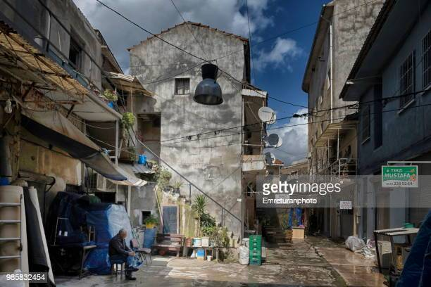 man sitting in a courtyard in kemeralti shopping district. - emreturanphoto stock pictures, royalty-free photos & images