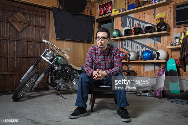 A man sitting in a garage with his motorcycle