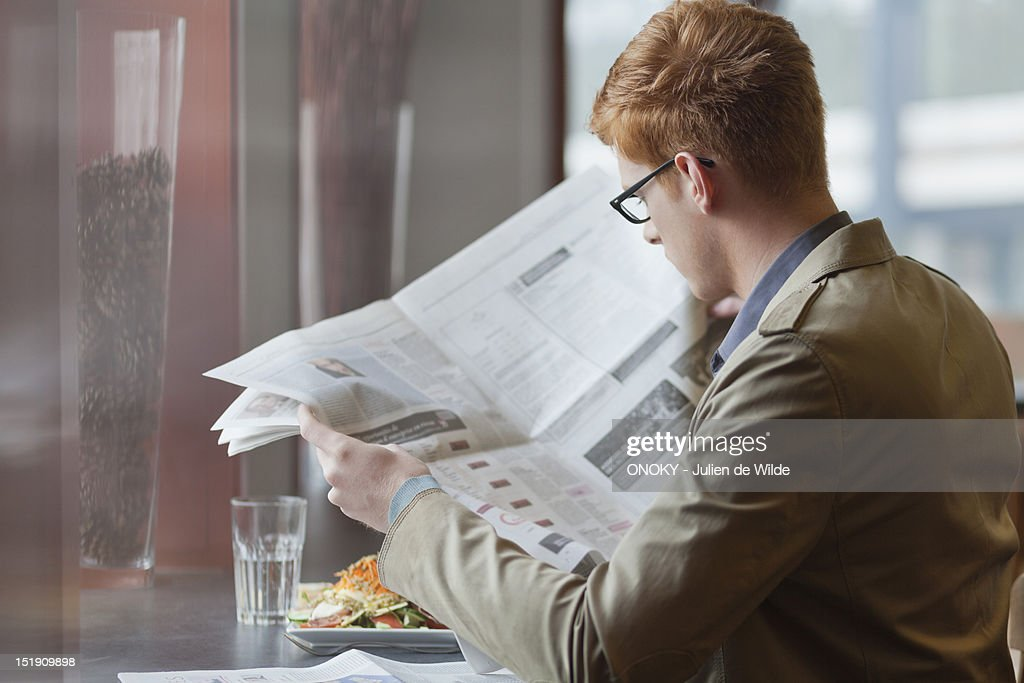 Man sitting in a restaurant and reading a newspaper : Stock Photo