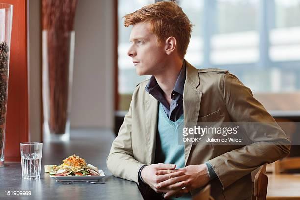 man sitting in a restaurant taking lunch - onoky stock-fotos und bilder