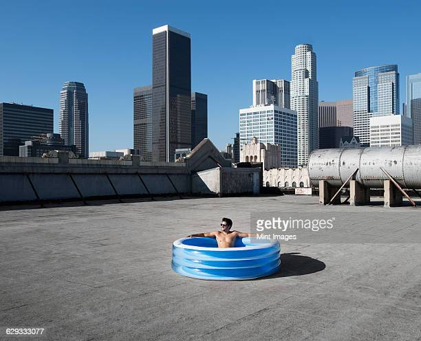 A man sitting in a small inflatable water pool on a city rooftop, cooling down.