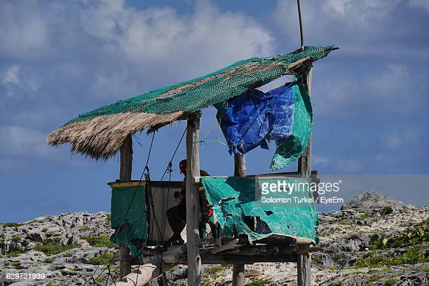 man sitting in abandoned hut against sky - solomon turkel stock pictures, royalty-free photos & images