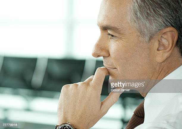 Man sitting in airport lounge, close-up of face