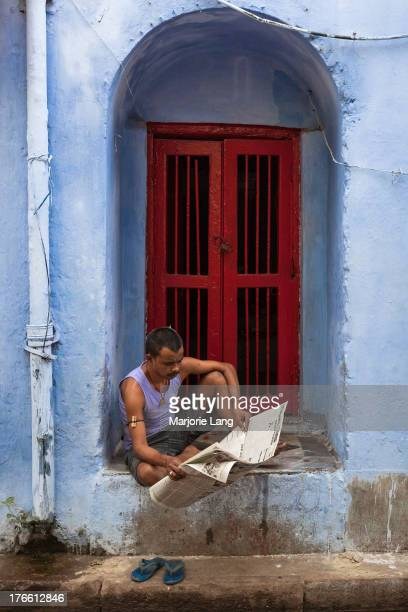 Man sitting in an alcove red door by a blue wall and reading a newspaper in Calcutta, West Bengal, India.