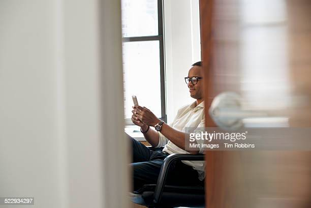 A man sitting in an office, checking his smart phone.