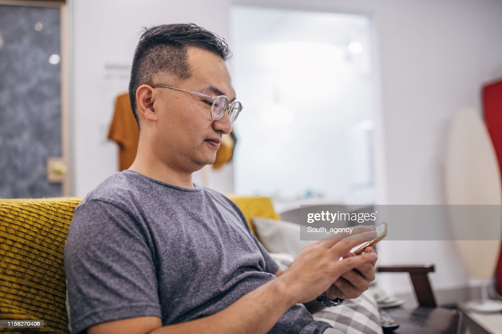 Man sitting in apartment and text messaging : Stock Photo
