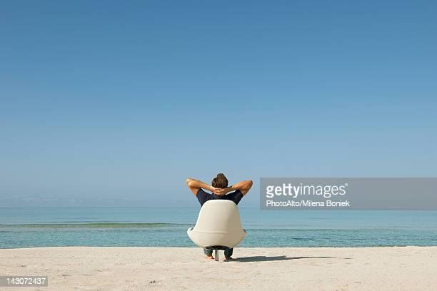 man sitting in armchair on beach looking at ocean, rear view - hombre de espaldas playa fotografías e imágenes de stock