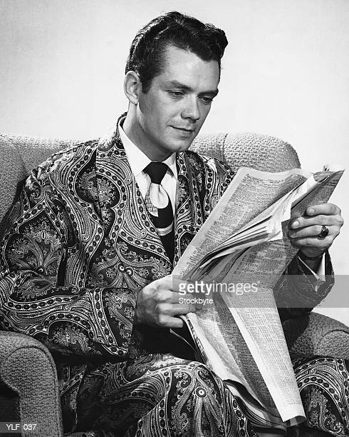 man sitting in armchair, reading newspaper - smoking jacket stock photos and pictures