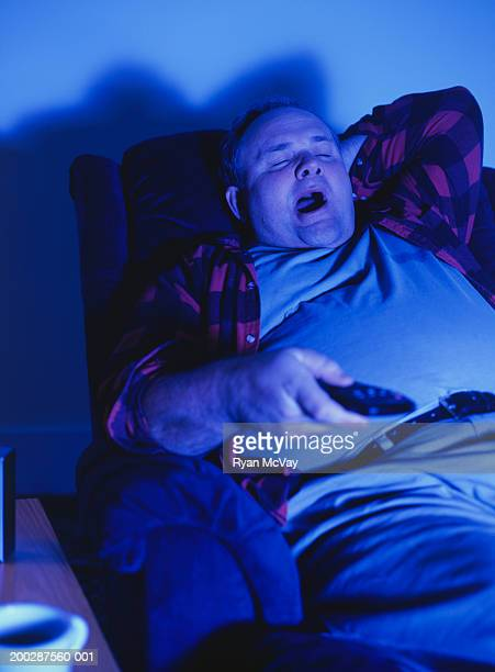 Man sitting in armchair yawning, watching television in living-room