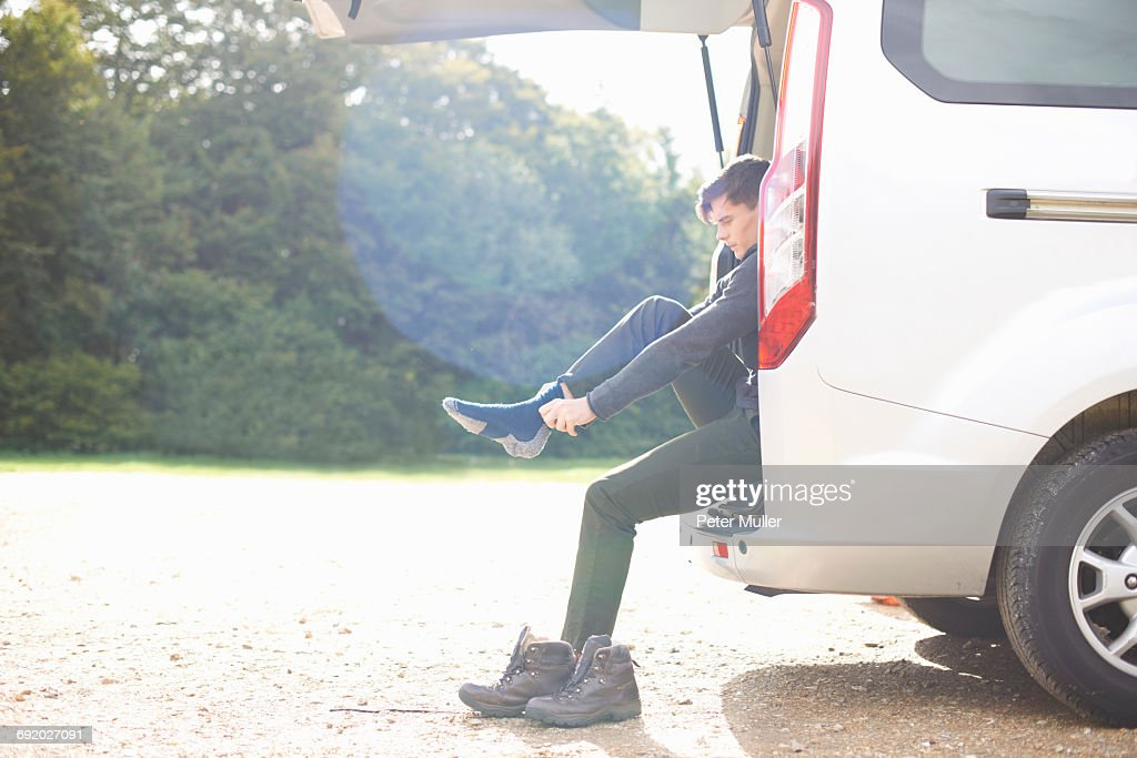 Man sitting in automobile boot putting on socks : Stock Photo