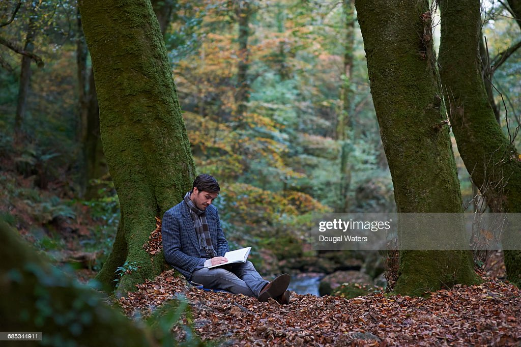 Man sitting in Autumn woodland reading book. : Stock Photo