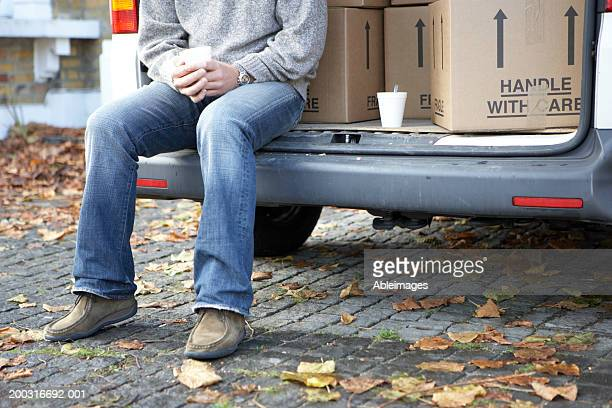 Man sitting in back of van holding cup, low section
