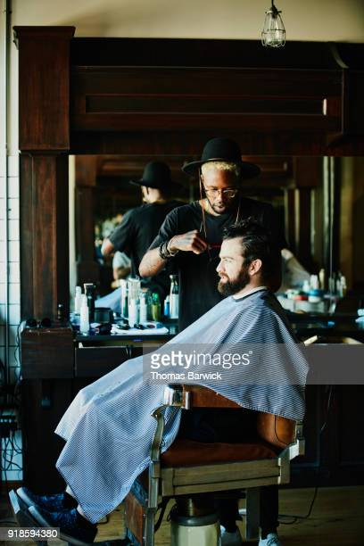 man sitting in barber shop receiving haircut - vertical stock pictures, royalty-free photos & images