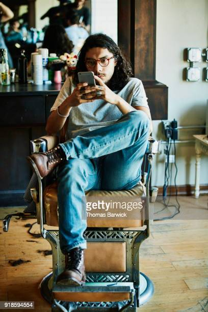 man sitting in barbers chair looking at phone while waiting for haircut - texas independence day stock pictures, royalty-free photos & images