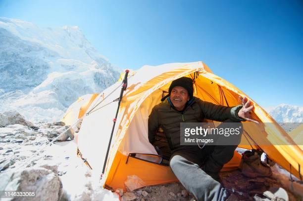 man sitting in base camp tent, everest, khumbu glacier, nepal - hardnekkigheid stockfoto's en -beelden