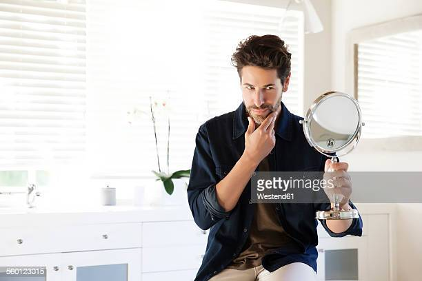 man sitting in bathroom looking at mirror - body care stock pictures, royalty-free photos & images