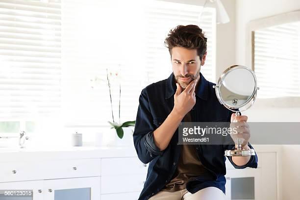 Man sitting in bathroom looking at mirror