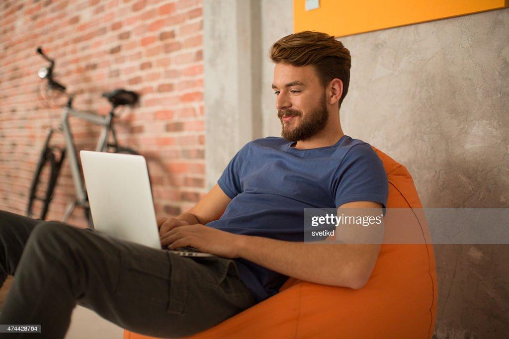 Man sitting in bean bag and using laptop. : Stock Photo