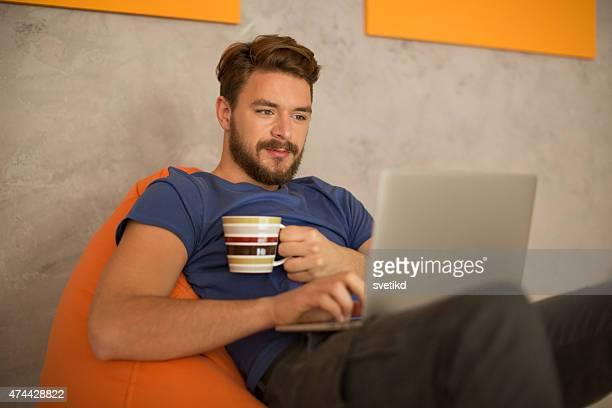 Man sitting in bean bag and using laptop.