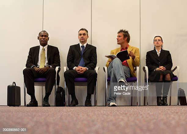 man sitting in between three people in bussiness attire, ground view - pantalon noir photos et images de collection
