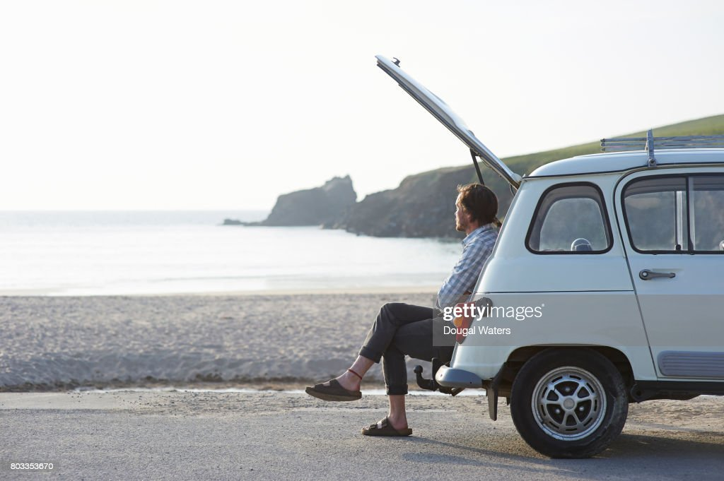 Man sitting in boot of retro car at beach. : Stock Photo