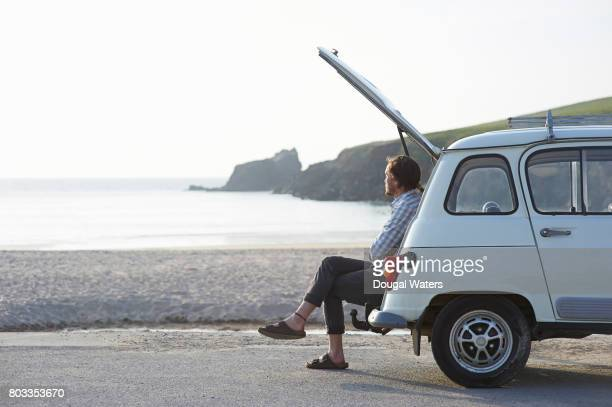 Man sitting in boot of retro car at beach.