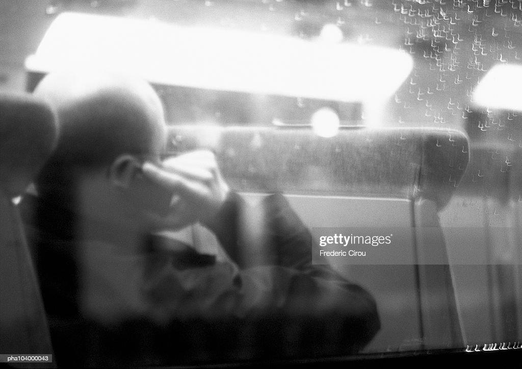 Man sitting in bus, viewed through window, rear view, blurred, b&w : Stockfoto