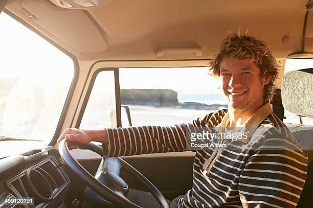 Man sitting in camper van beside coast.