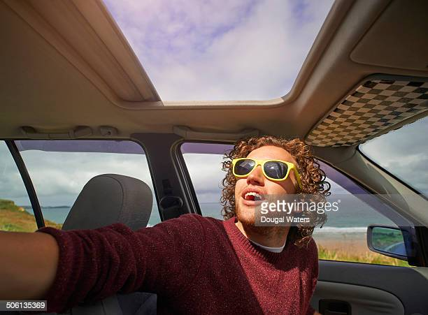 Man sitting in car and looking out of sunroof