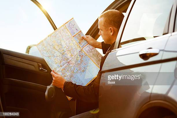 Man sitting in car and reading map