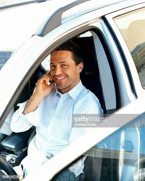 Man sitting in car and talking on mobile phone