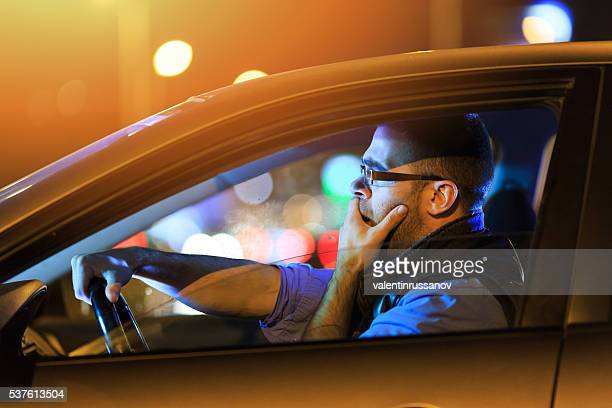 Man sitting in car and yawning by night