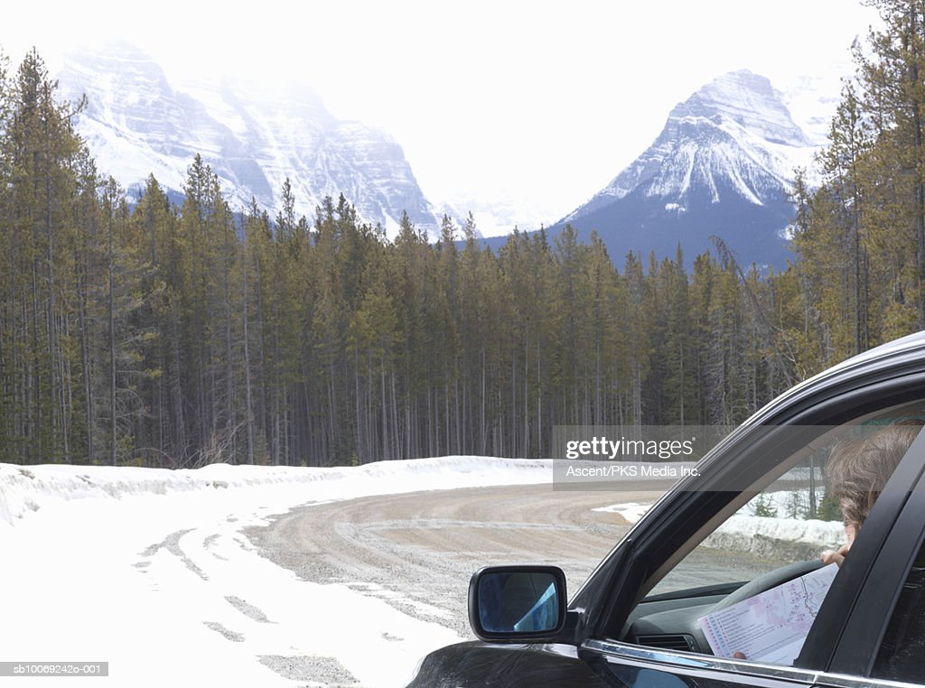 Man sitting in car holding map on snowy road : Stockfoto