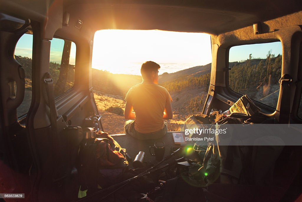 Man sitting in car looking at sunset in mountains : Stock Photo