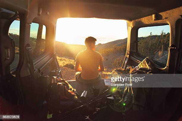 Man sitting in car looking at sunset in mountains