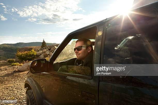 Man sitting in car overlooking rural landscape