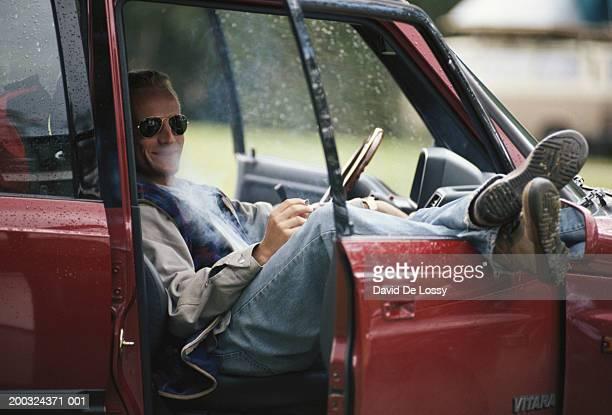 Man sitting in car smoking
