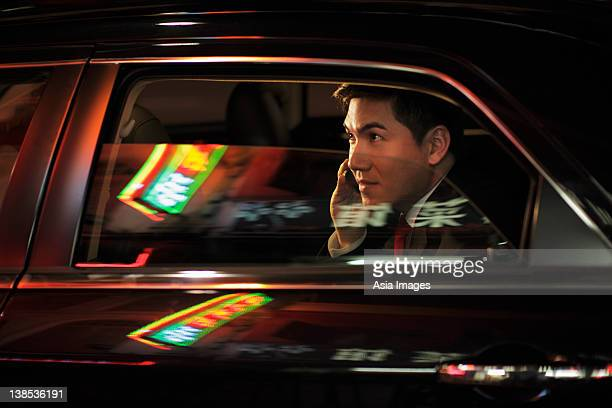 Man sitting in car talking on phone. Chinese characters reflected on the windows