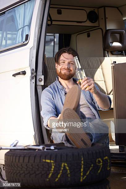man sitting in car with tyre and beer bottle - puncturing stock pictures, royalty-free photos & images
